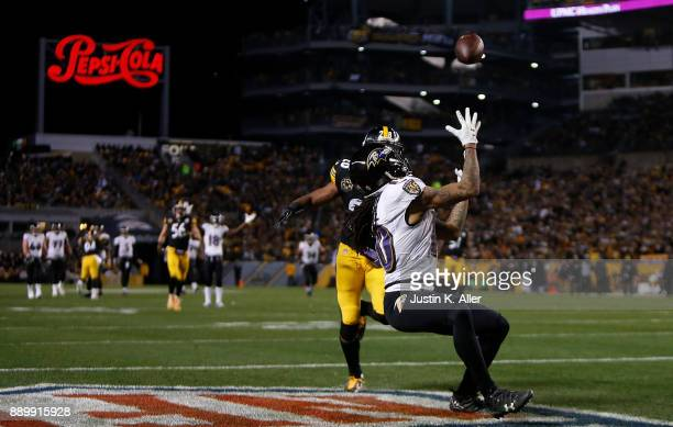 Chris Moore of the Baltimore Ravens makes a catch for a 30 yard touchdown reception while being defended by Sean Davis of the Pittsburgh Steelers in...
