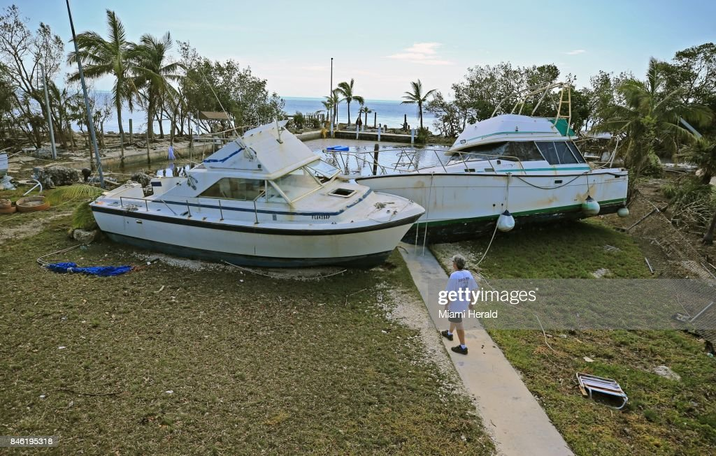 Chris Morgan inspects the large boats that beached onto the property she in stayed during Hurricane Irma's storm surge in Key Largo, Fla., on Tuesday, Sept. 12, 2017.