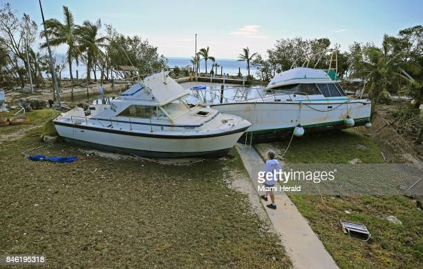 Chris Morgan inspects the large boats that beached onto the property she in stayed during Hurricane Irma's storm surge in Key Largo Fla on Tuesday...