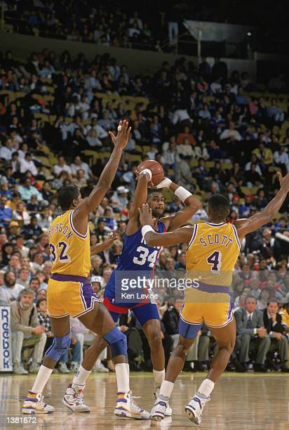 Chris Morris of the New Jersey Nets looks to pass the ball over the defense of Magic Johnson and Byron Scott of the Los Angeles Lakers during the NBA...