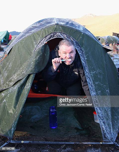 Chris Moyles brushes his teeth on the second day of The BT Red Nose Climb of Kilimanjaro on March 3 2009 in Arusha Tanzania Celebrities Ronan Keating...