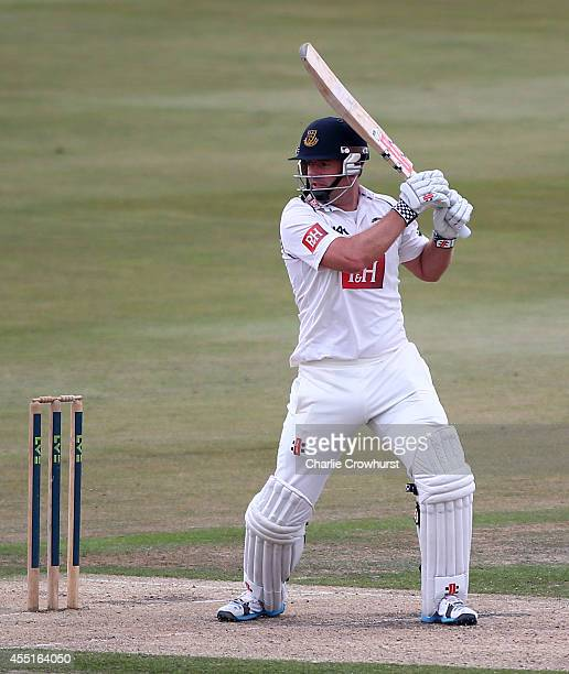 Chris Nash of Sussex hits out while Jos Buttler of Lancashire looks on during day two of the LV County Championship match between Sussex and...