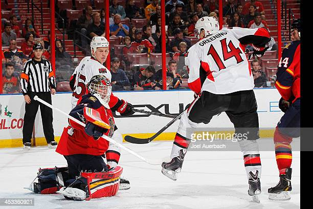 Chris Neil looks back as Colin Greening of the Ottawa Senators lifts the puck over goaltender Tim Thomas of the Florida Panthers to score the lead...