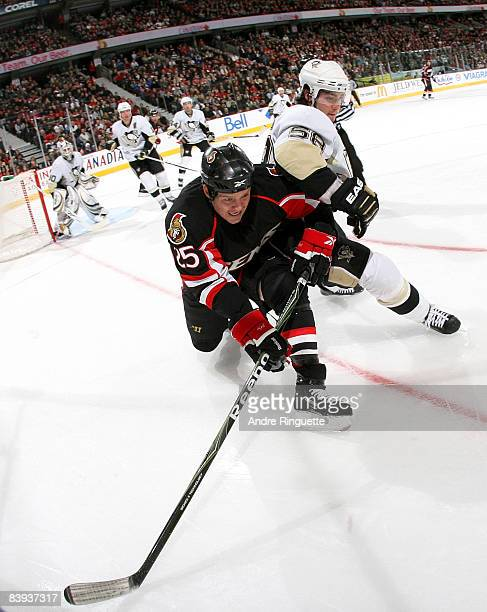 Chris Neil of the Ottawa Senators battles with Kris Letang of the Pittsburgh Penguins for position along the boards at Scotiabank Place on December...
