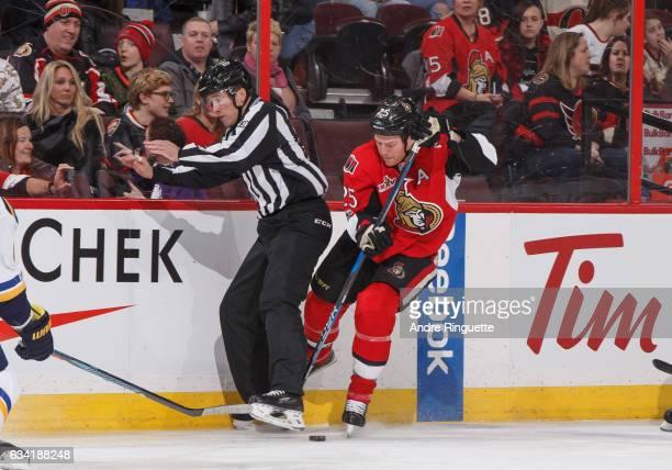 Chris Neil of the Ottawa Senators bumps into linesman Steve Barton as he stickhandles the puck against the St Louis Blues at Canadian Tire Centre on...