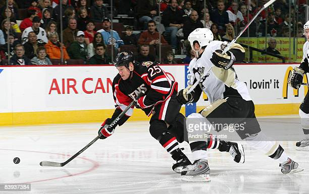 Chris Neil of the Ottawa Senators controls the puck against Brooks Orpik of the Pittsburgh Penguins at Scotiabank Place on December 6, 2008 in...