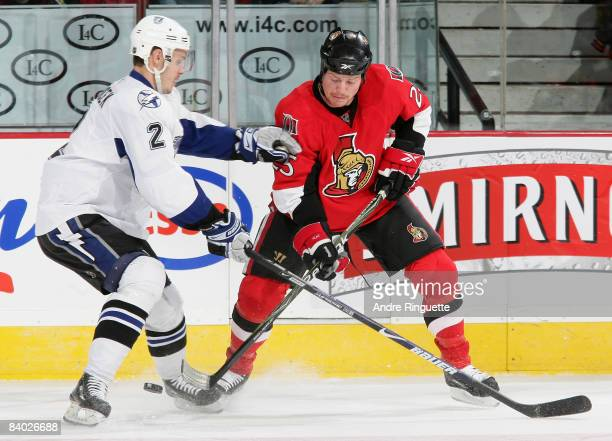 Chris Neil of the Ottawa Senators controls the puck against Lukas Krajicek of the Tampa Bay Lightning at Scotiabank Place on December 13 2008 in...
