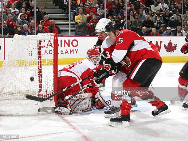 Chris Neil of the Ottawa Senators digs for a rebound against Chris Osgood and Andreas Lilja of the Detroit Red Wings at Scotiabank Place on October...
