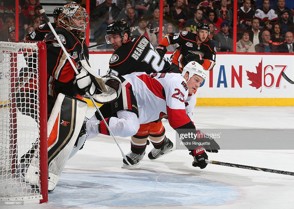 Chris Neil #25 of the Ottawa Senators gets upended by Francois Beauchemin #23 of the Anaheim Ducks in front of the net of Frederik Andersen #31 of the Ducks at Canadian Tire Centre on October 25, 2013 in Ottawa, Ontario, Canada.