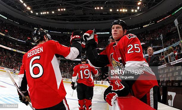 Chris Neil of the Ottawa Senators high fives teammate Wade Redden from the bench for Redden's first period goal against the Montreal Canadiens at...