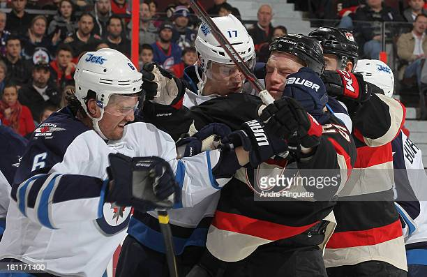 Chris Neil of the Ottawa Senators is pushed away from the crease after a whistle by Ron Hainsey and James Wright of the Winnipeg Jets on February 9...