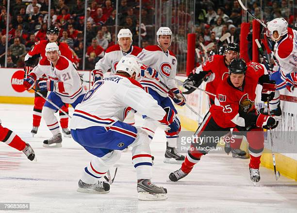 Chris Neil of the Ottawa Senators skates over the blueline sending a backhand pass towards the middle past Michael Komisarek of the Montreal...