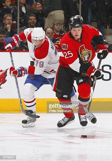 Chris Neil of the Ottawa Senators skates with the puck while being pressured by Andrei Markov of the Montreal Canadiens during their NHL game on...