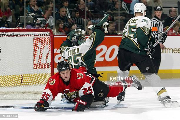 Chris Neil of the Ottawa Senators trips over goalie Marty Turco of the Dallas Stars on December 15 2005 at the Corel Centre in Ottawa Ontario Canada...