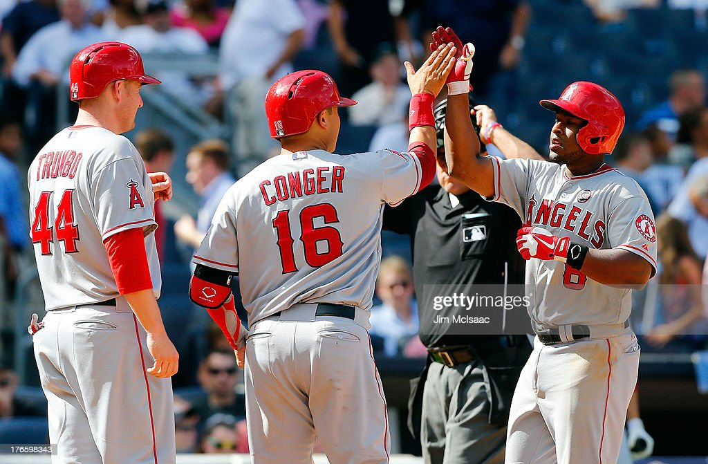 Chris Nelson #8 of the Los Angeles Angels of Anaheim celebrates his eighth inning grand slam against the New York Yankees with teammates Mark Trumbo #44 and Hank Conger #16 at Yankee Stadium on August 15, 2013 in the Bronx borough of New York City.