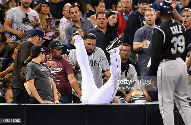 Chris Nelson of the San Diego Padres flips into the stands as he makes the catch on a foul ball hit by Charlie Blackmon of the Colorado Rockies...