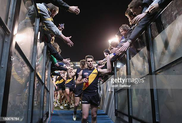 Chris Newman captain of the Tigers leads his team from the field after winning the round 22 AFL match between the Richmond Tigers and the Essendon...