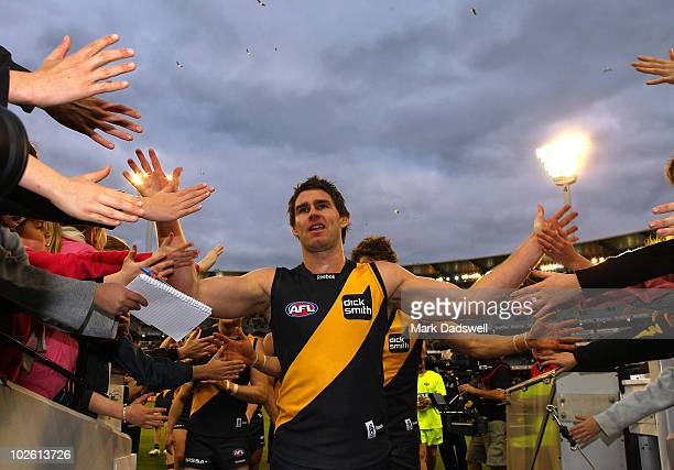 Chris Newman captain of the Tigers leads the team off after their win in the round 14 AFL match between the Richmond Tigers and the Sydney Swans at...