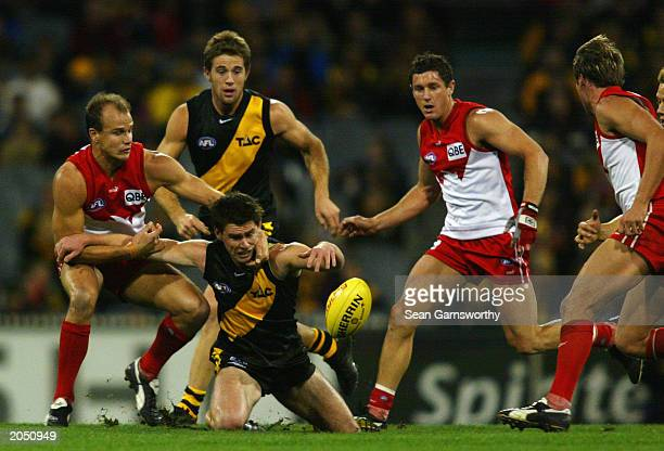 Chris Newman of the Tigers comes under pressure from Matthew Nicks of the Swans during the round 10 AFL match between the Richmond Tigers and the...