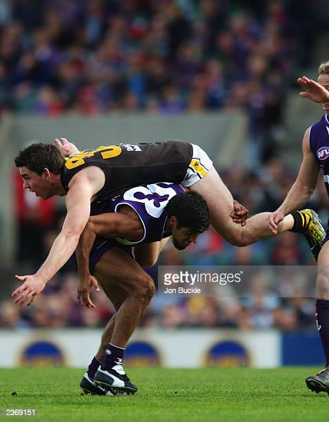 Chris Newman of the Tigers crashes over the back of Jeff Farmer of the Dockers during the round 18 AFL match between the Fremantle Dockers and the...
