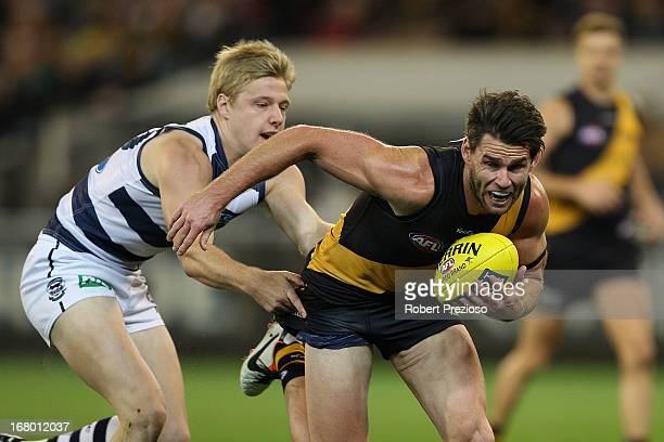 Chris Newman of the Tigers is tackled during the round six AFL match between the Richmond Tigers and the Geelong Cats at Melbourne Cricket Ground on...