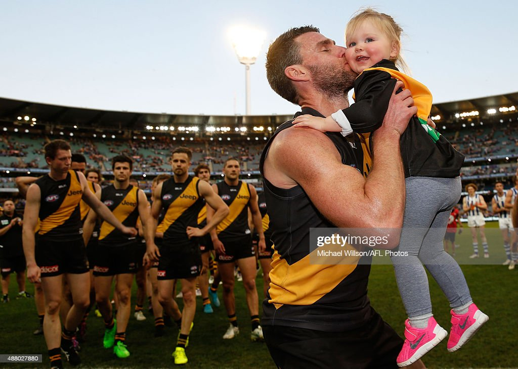 Chris Newman of the Tigers walks from the field after his last match with his daughter during the 2015 AFL First Elimination Final match between the Richmond Tigers and the North Melbourne Kangaroos at the Melbourne Cricket Ground, Melbourne, Australia on September 13, 2015.