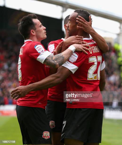 Chris O'Grady of Barnsley celebrates scoring the opening goal with teammates during the npower Championship match between Huddersfield Town and...