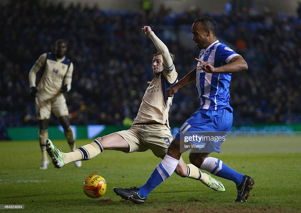 Chris O'Grady of Brighton & Hove Albion is tackled by Casper Sloth of Leeds United during the Sky Bet Championship match between Brighton & Hove Albion and Leeds United at Amex Stadium on February 24, 2015 in Brighton, England.