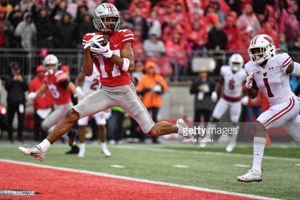 Chris Olave of the Ohio State Buckeyes catches a 27yard touchdown pass in front of Faion Hicks of the Wisconsin Badgers in the second quarter at Ohio...