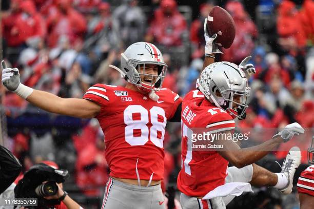 Chris Olave of the Ohio State Buckeyes celebrates his second quarter touchdown catch against the Wisconsin Badgers with Jeremy Ruckert of the Ohio...