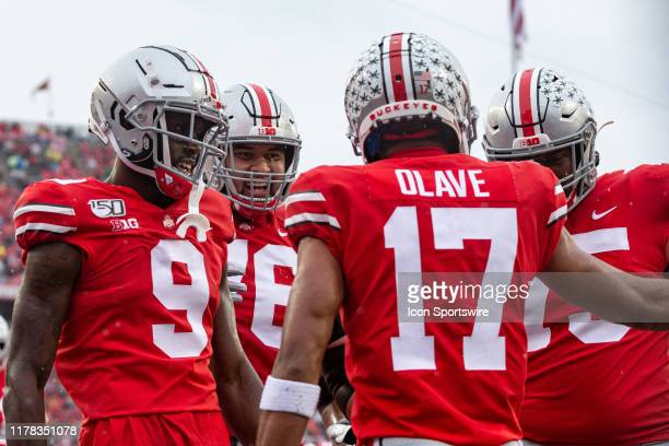 Chris Olave of the Ohio State Buckeyes celebrates with Binjimen Victor of the Ohio State Buckeyes Branden Bowen of the Ohio State Buckeyes and Thayer...