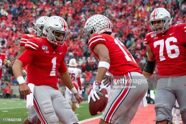 Chris Olave of the Ohio State Buckeyes celebrates with Justin Fields of the Ohio State Buckeyes after scoring a touchdown during game action between...