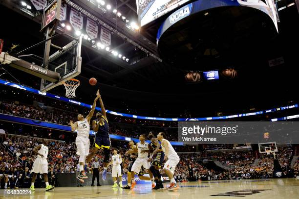 Chris Otule of the Marquette Golden Eagles shoots the ball over Julian Gamble of the Miami Hurricanes during the East Regional Round of the 2013 NCAA...