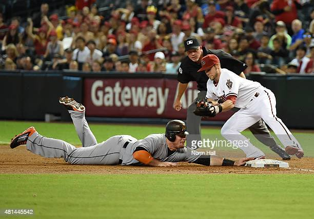 Chris Owings of the Arizona Diamondbacks attempts to tag out Justin Bour of the Miami Marlins at first base during the first inning at Chase Field on...