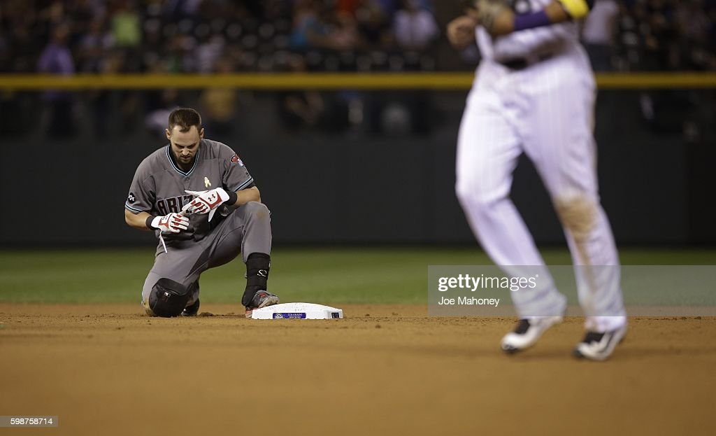 Chris Owings #16 of the Arizona Diamondbacks kneels at second base after being tagged out by DJ LeMahieu #9 of the Colorado Rockies in the seventh inning of a seventh inning of a baseball game at Coors Field on September 2, 2016 in Denver, Colorado.