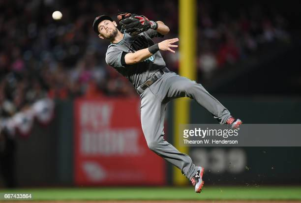 Chris Owings of the Arizona Diamondbacks makes an off balance throw but not in time to first base to get Eduardo Nunez of the San Francisco Giants in...