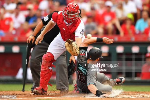 Chris Owings of the Arizona Diamondbacks slides home safely in the second inning as catcher Stuart Turner of the Cincinnati Reds misses the throw at...