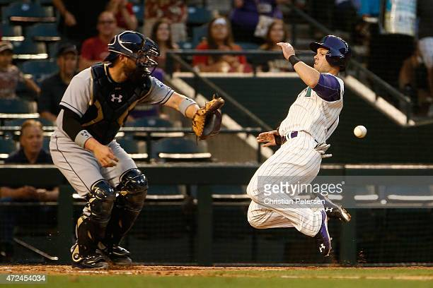 Chris Owings of the Arizona Diamondbacks slides in to score a first inning run past catcher Derek Norris of the San Diego Padres during the MLB game...