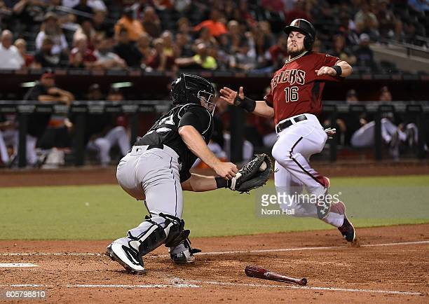 Chris Owings of the Arizona Diamondbacks slides safely into home plate ahead of the tag by Tom Murphy of the Colorado Rockies during the fifth inning...