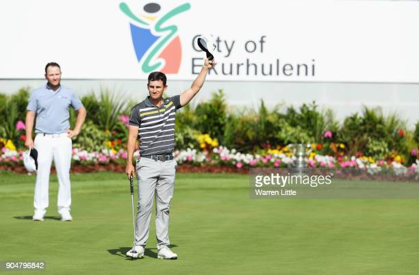 Chris Paisley of England celebrates victory on the 18th green watched by Branden Grace of South Africa during day four of the BMW South African Open...