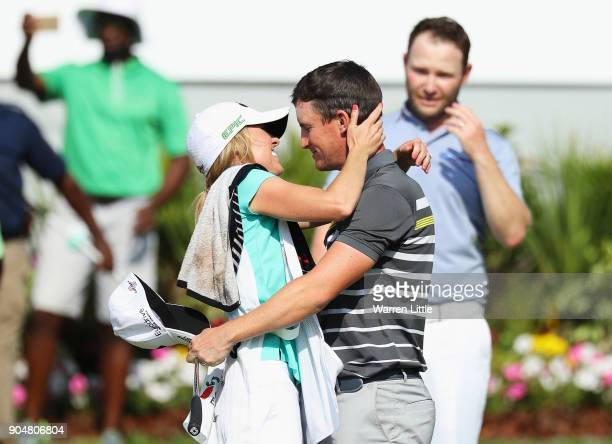 Chris Paisley of England celebrates victory with caddie and wife Keri on the 18th green watched by Branden Grace of South Africa during day four of...