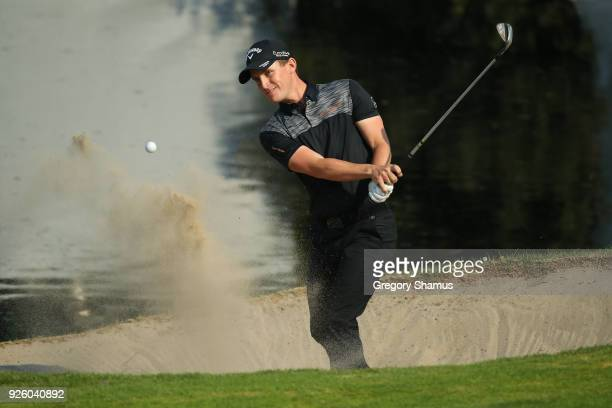 Chris Paisley of England hits from a plays a shot from the green of hole side bunker on17th hole during the first round of World Golf...