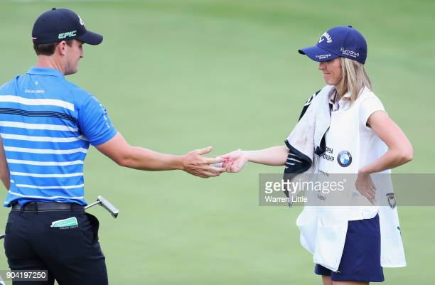 Chris Paisley of England takes a ball from caddie and wife Keri on the 18th green during day two of the BMW South African Open Championship at...