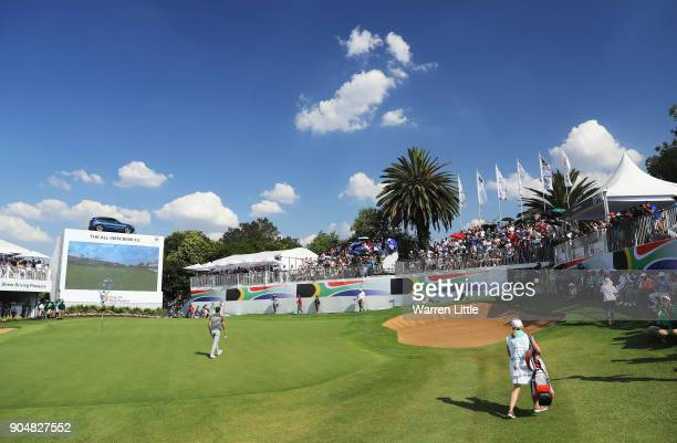 Chris Paisley of England walks on the 18th green with caddie and wife Keri on the way to victory during day four of the BMW South African Open...