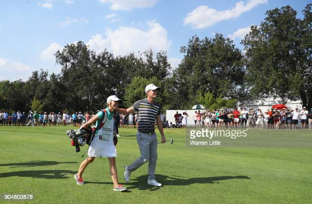 Chris Paisley of England walks to the 18th green with caddie and wife Keri on the way to victory during day four of the BMW South African Open...