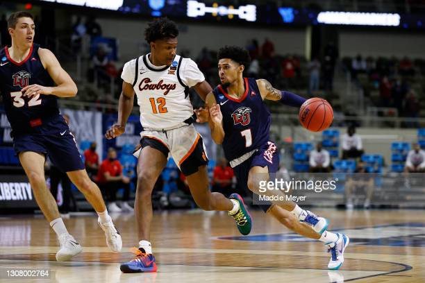 Chris Parker of the Liberty Flames drives past Matthew-Alexander Moncrieffe of the Oklahoma State Cowboys during the first half in the first round...