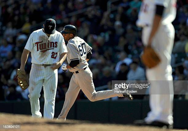 Chris Parmelee and Anthony Swarzak of the Minnesota Twins look on as Chris Dickerson of the New York Yankees rounds the bases after hitting a tworun...