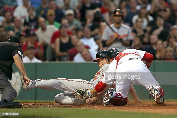 Chris Parmelee of the Baltimore Orioles is tagged out by Sandy Leon of the Boston Red Sox trying top steal home in the third inning at Fenway Park on...