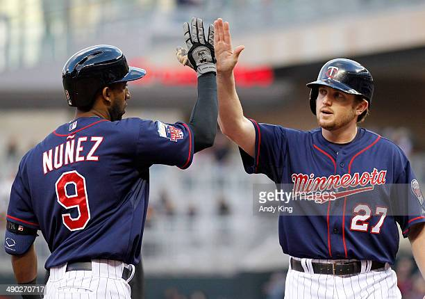 Chris Parmelee of the Minnesota Twins congratulates Eduardo Nunez of the Minnesota Twins after Nunez hit a home run in the second inning and the...
