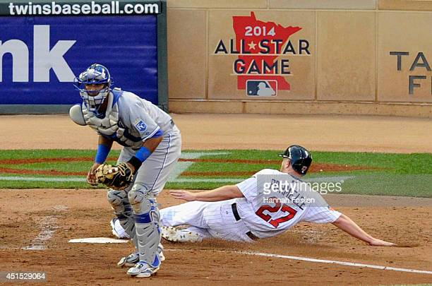 Chris Parmelee of the Minnesota Twins slides safely past Salvador Perez of the Kansas City Royals to score a run during the fifth inning of the game...